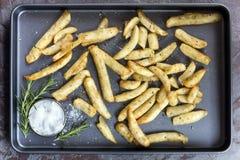 土豆楔子有在烤箱盘子的罗斯玛丽和海盐顶视图 库存图片