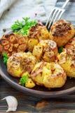 土豆烘烤了用大蒜、麝香草和绿色荷兰芹 库存照片
