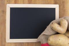 土豆爱-在黑板前面的心形的土豆 库存图片