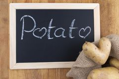 土豆爱-在黑板前面的心形的土豆 图库摄影