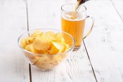 土豆片和杯在一张木桌上的啤酒 库存照片