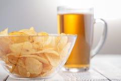 土豆片和杯在一张木桌上的啤酒 库存图片