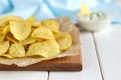 土豆片用在一张白色木桌上的调味汁 免版税库存照片
