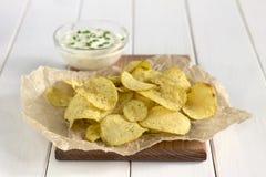土豆片用在一张白色桌上的调味汁 免版税库存图片