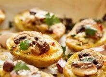 土豆皮用蘑菇,葱,草本装载了并且熔化了乳酪 库存图片