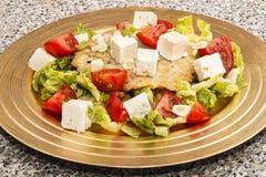 土豆薄烤饼、地中海样式用蕃茄,沙拉和山羊 库存照片
