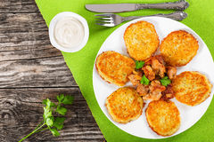 土豆薄烤饼用在白色盘的被炖的猪肉 免版税库存照片