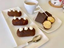 土豆蛋糕、裁减在两蛋糕流行音乐和巧克力片 在板材的谎言 附近一杯咖啡用牛奶 图库摄影