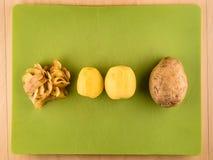 土豆,皮肤在绿色塑料委员会的中心 库存照片