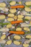 年轻土豆,红萝卜,葱,胡椒,大蒜在烘烤盘子为烘烤在烤箱做准备 顶视图 免版税库存照片