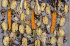 年轻土豆,红萝卜,葱,胡椒,大蒜在烤箱烘烤了 顶视图 图库摄影