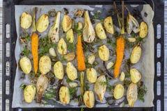 年轻土豆,红萝卜,葱,胡椒,大蒜在烤箱烘烤了 顶视图 库存照片