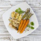年轻土豆,红萝卜,葱,胡椒,大蒜在白色板材的烤箱烘烤了 顶视图 库存图片