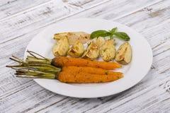 年轻土豆,红萝卜,葱,胡椒,大蒜在白色板材的烤箱烘烤了 免版税库存照片
