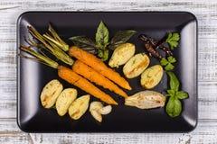 年轻土豆,红萝卜,葱,胡椒,大蒜在黑色的盘子的烤箱烘烤了 顶视图 库存照片