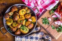 土豆 土豆烤了 与熏制的烟肉大蒜盐的美国土豆以子弹密击小茴香莳萝荷兰芹-草本装饰 库存图片