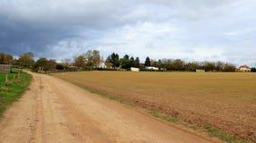 土路和农田有雨云的 免版税库存图片