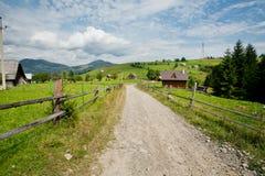 土路在一个绿色村庄在蓝天和白色云彩下 免版税库存照片