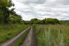 土路在乡下,草,树,与云彩的天空 库存照片