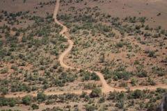 土路绕通过干旱的风景 库存图片