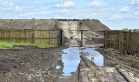 土路,露天被存放的水池和很多研为闭合的篱芭 免版税库存图片