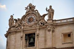 圣伯多禄大教堂梵蒂冈的 左角度图由圣徒和一个大时钟有些雕象装饰了 库存照片