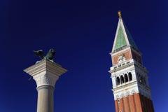 圣塔指示钟楼和威尼斯狮子雕象  免版税库存图片