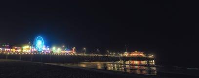 圣塔蒙尼卡在晚上照亮的码头木板走道 库存图片