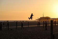 圣塔蒙尼卡,加利福尼亚,美国04 01 2017年在日落期间的slackline跳跃的人在海滩 免版税库存图片