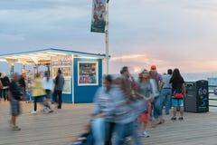 圣塔蒙尼卡移动在日落的码头人 免版税库存图片