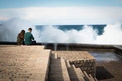 圣塞瓦斯蒂安,西班牙- 2018年3月16日:夫妇坐海水石墙赞赏的风景巨大的飞溅挥动 免版税库存图片