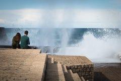 圣塞瓦斯蒂安,西班牙- 2018年3月16日:夫妇坐海水石墙赞赏的风景巨大的飞溅挥动 免版税库存照片
