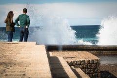 圣塞瓦斯蒂安,西班牙- 2018年3月16日:夫妇坐海水石墙赞赏的风景巨大的飞溅挥动 库存照片
