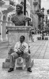 圣多明哥,多米尼加共和国 坐在Bartolomeo冒号雕象基地的一个人,位于康德街道 b/n版本 免版税库存图片