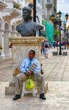 圣多明哥,多米尼加共和国 坐在Bartolomeo冒号雕象基地的一个人,位于康德街道 b/n版本 库存照片