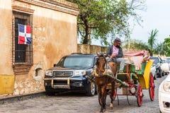 圣多明哥,多米尼加共和国- 2017年8月8日:一个减速火箭的支架的马车夫在城市街道上 复制文本的空间 免版税库存图片