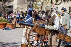 圣安东尼奥,得克萨斯- 2018年3月2日-作为19世纪战士打扮的人射击争斗的再制定的古色古香的大炮  免版税库存图片