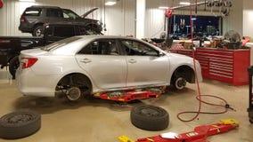 圣安东尼奥, TX - 2016年11月23日-在安排丰田的经销商的汽车轮胎和闸被替换 汽车暂停 在红色电梯上 库存照片