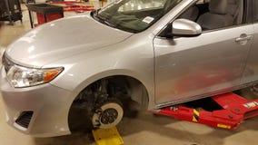 圣安东尼奥, TX - 2016年11月23日-在安排丰田的经销商的汽车轮胎和闸被替换 汽车暂停 在红色电梯上 库存图片
