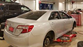圣安东尼奥, TX - 2016年11月23日-在安排丰田的经销商的汽车轮胎和闸被替换 汽车暂停 在红色电梯上 免版税库存照片