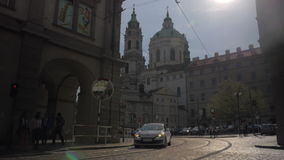 圣尼古拉教会老有汽车的镇中心在布拉格在太阳天和路看法在前景,捷克 股票录像