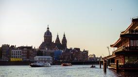 圣尼古拉斯大教堂老中心区和典型的荷兰房子和游览小船的,阿姆斯特丹主要天主教会, 免版税库存图片