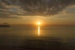 圣山剪影在日出或日落与光线和海全景的在希腊 免版税库存图片