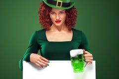 圣帕特里克天有啤酒杯的红头发人女孩 年轻性感的oktoberfest妇女,戴一个礼服和绿色帽子有白色横幅的 库存图片