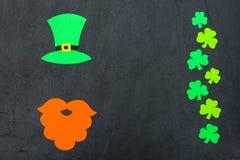 圣帕特里克` s天题材五颜六色的水平的横幅 绿色妖精帽子、胡子和三叶草叶子在黑背景 毛毡cra 库存图片