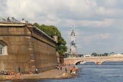 圣彼得堡,俄罗斯:2017年8月24日:休息在花岗岩彼得和保罗堡垒边界墙的人们在圣彼得堡 库存照片