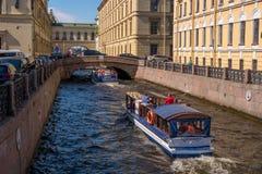 圣彼得堡,俄罗斯- 2017年6月17日:游船沿冬天运河移动在偏僻寺院附近 库存图片