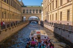 圣彼得堡,俄罗斯- 2017年6月17日:游船沿冬天运河移动在偏僻寺院附近 库存照片
