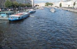 圣彼得堡,俄罗斯2016年9月10日:游览船在Fontanka河  从Anichkov桥梁的看法在圣彼得 免版税图库摄影