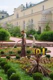 圣彼得堡,俄罗斯- 205 6月05, :妇女花匠浇灌的花在偏僻寺院少校美术馆庭院里  库存图片